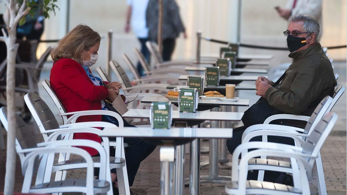 Personas con mascarilla en la terraza de un bar, en Málaga.