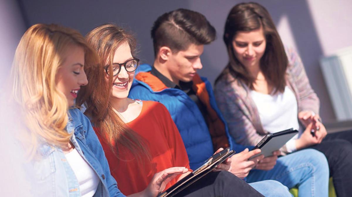 Estudiantes universitarios repasan sus apuntes en tabletas móviles.