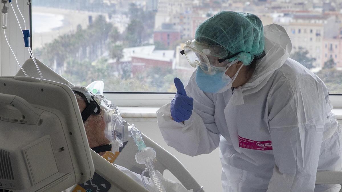 Una doctora anima a un paciente ingresado en la planta covid del Hospital del Mar.