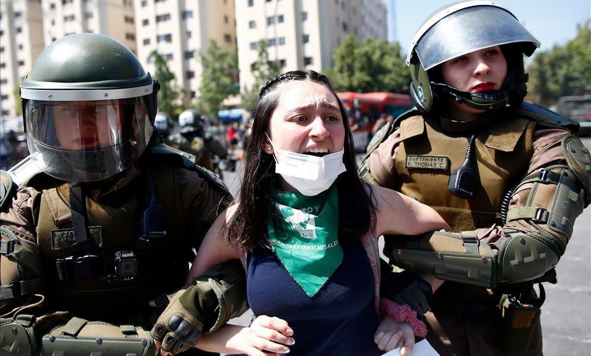 Dos agentes antidisturbios detienen a una joven manifestante en Santiago de Chile.