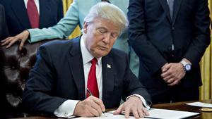 El presidente de Estados Unidos,Donald Trump, firma una orden ejecutiva en el despacho oval.