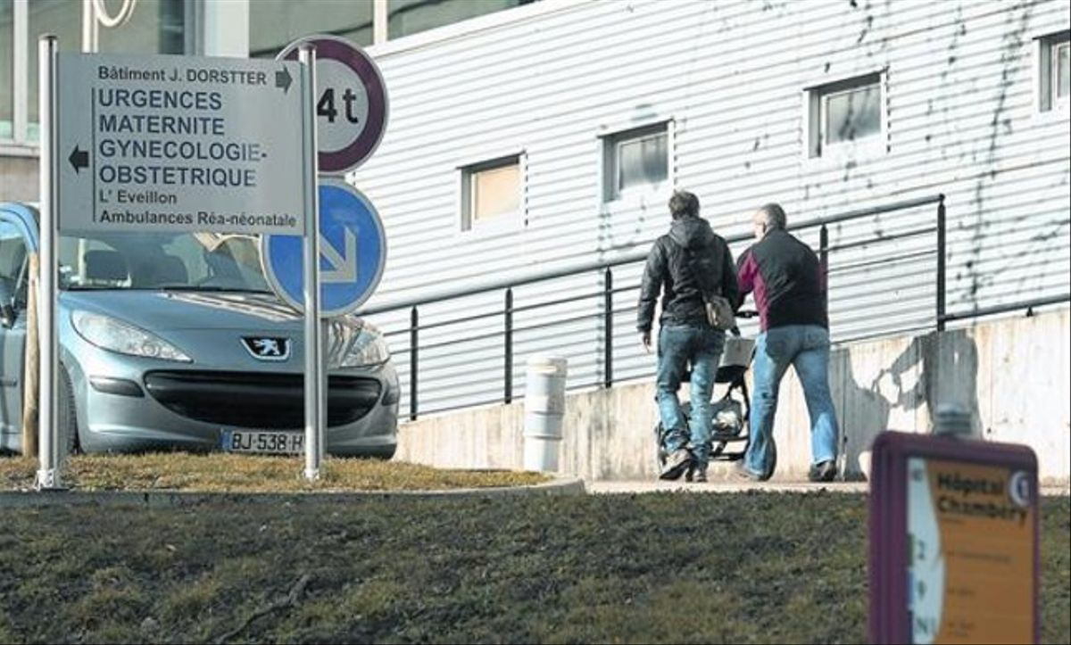 Dos personas se dirigen con un cochecito de bebé a la puerta de entrada del hospital de Chambéry, en los Alpes franceses.