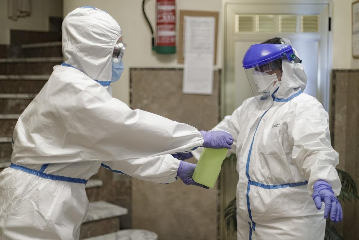 Personal sanitario se desinfecta en el interior de una residencia de ancianos de Madrid.