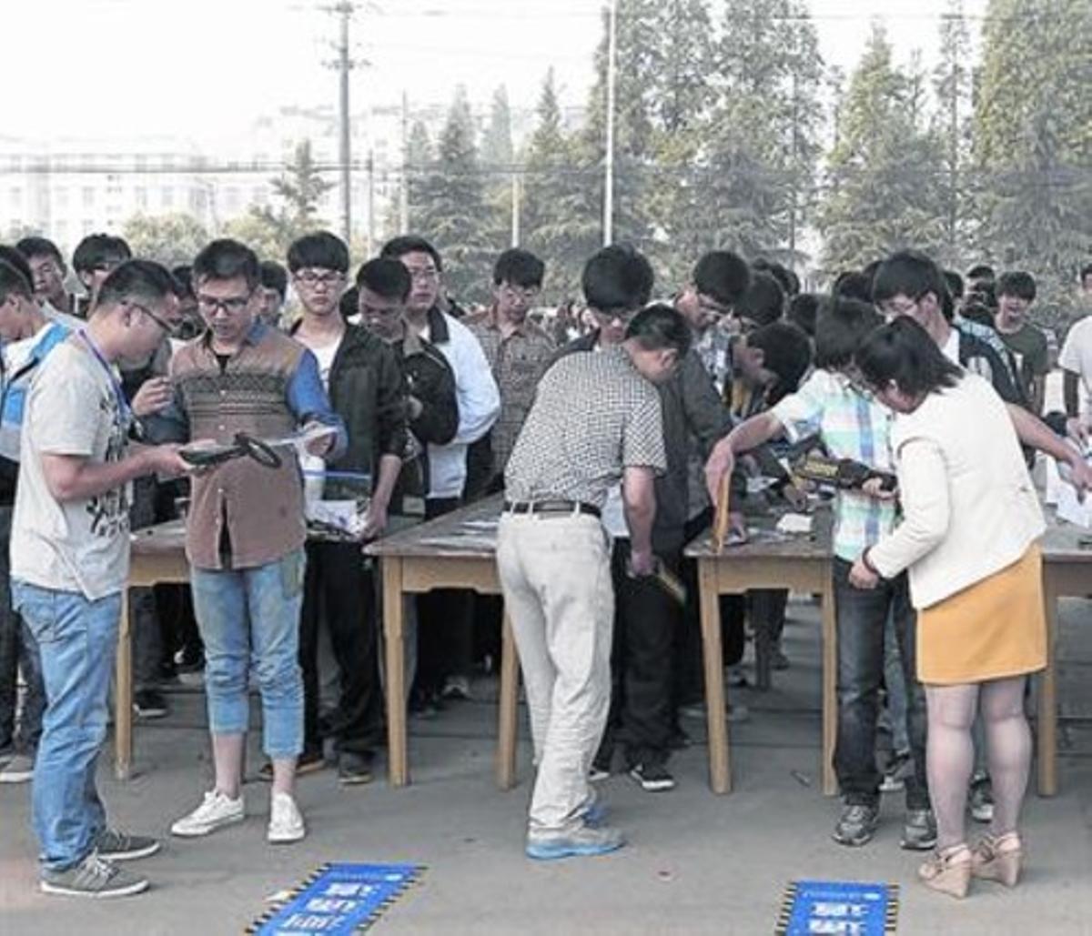 Vigilancia . Control de seguridad a alumnos antes del 'gaokao' (selectividad), en Ganyu (China).