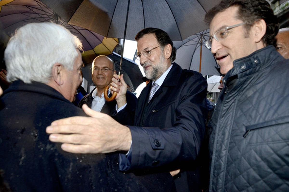 El presidente del Partido Popular y candidato a la presidencia del Gobierno, Mariano Rajoy, conversa con un hombre acompañado por el presidente de la Xunta de Galicia, Alberto Núñez Feijóo (derecha) y por el presidente provincial del partido, Manuel Baltar.