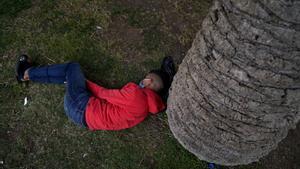 Un joven migrante duerme en un parque cercano al puerto de Ceuta.