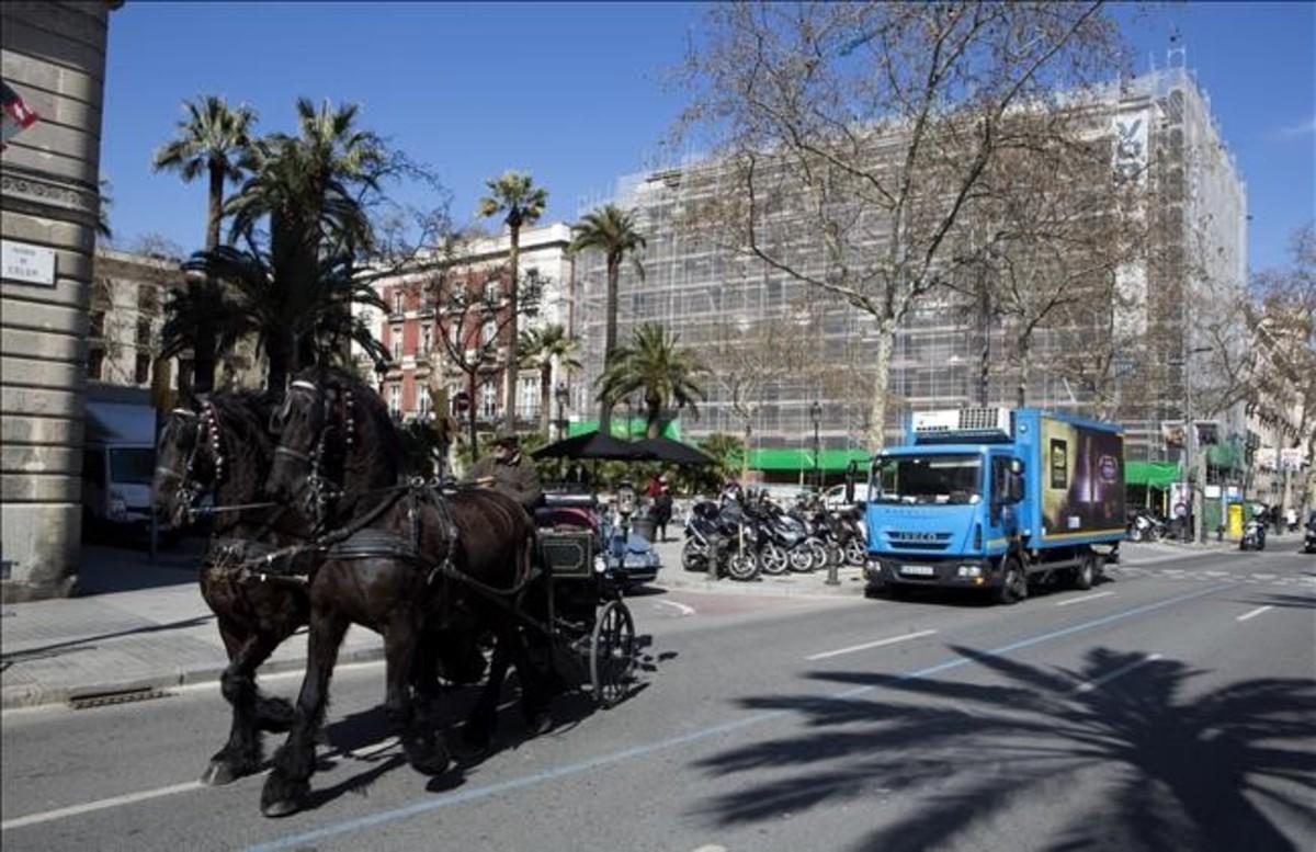 Un carruaje para turistas circula por el paseo de Colón a la altura de Duc de Medinaceli.