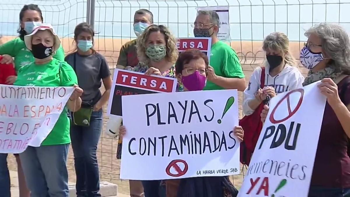 Vecinos de Sant Adrià de Besòs protestan ante la playa contaminada cerrada.