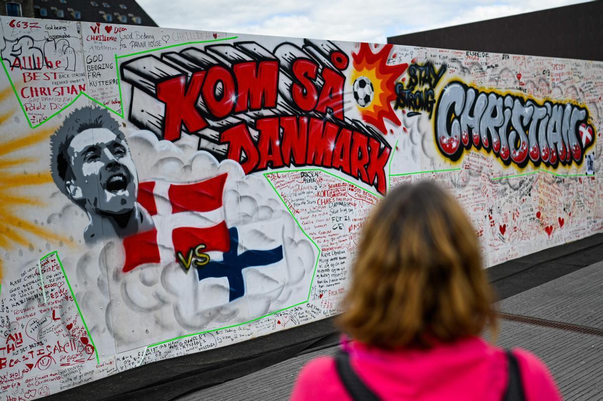 Una persona observa el mural pintado en Copenhague con mensajes escritos por la afición danesa.