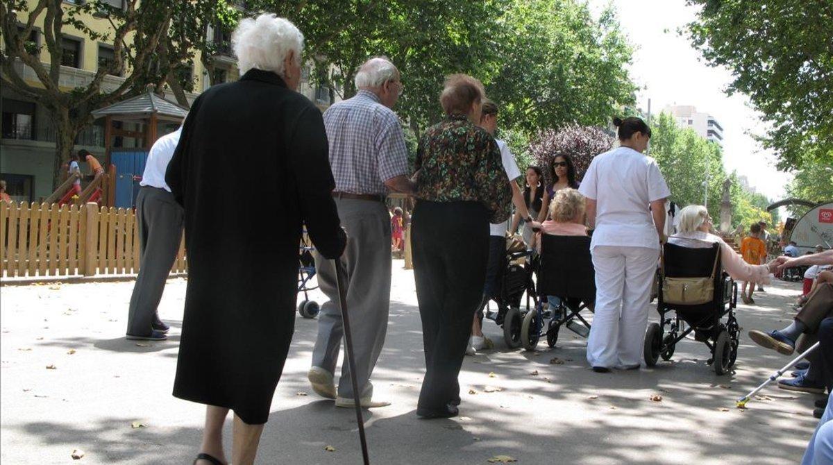 Un grupo de ancianos pasea por Paseo de Sant Joan.