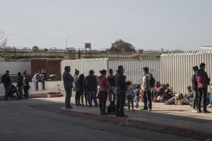 Un grupo de migrantes hacen cola en El Chaparral, en la frontera entre México y Estados Unidos buscando información sobre el proceso de asilo.