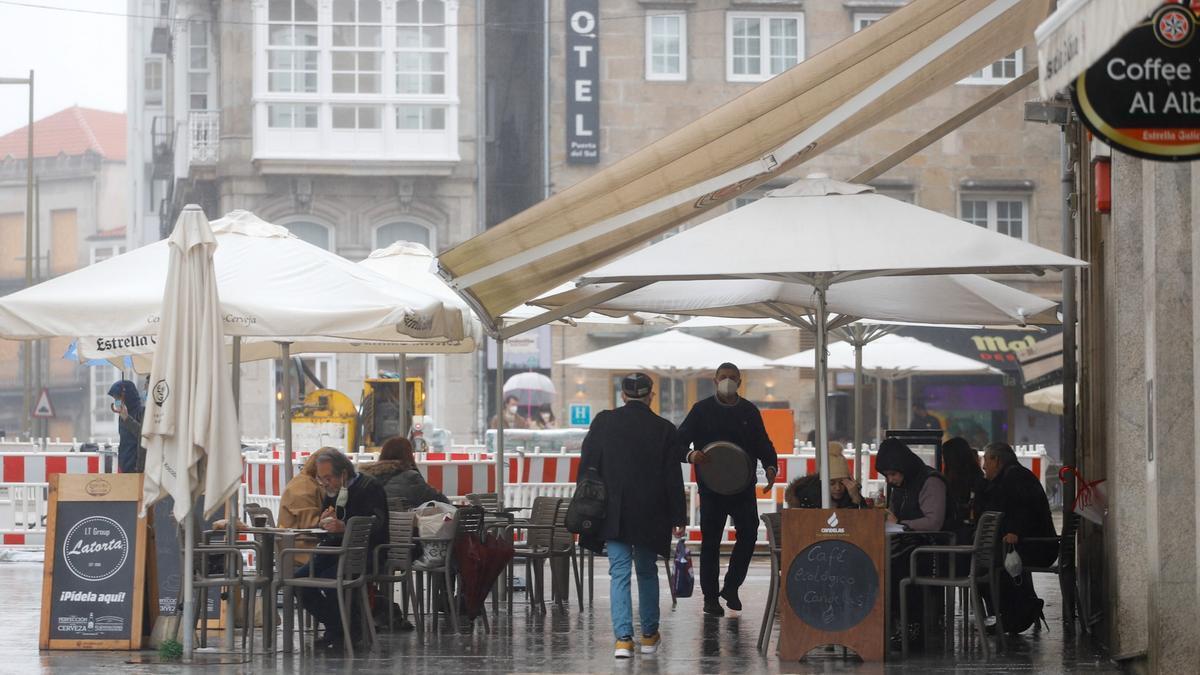 Varias personas, en la terraza de un bar un día antes del cierre de la hostelería, en Vigo, este martes.