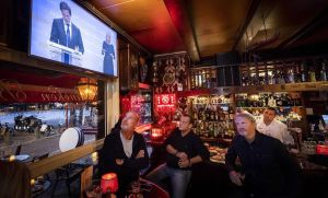 Empleados del café Marcella, en Amsterdam, siguen el mensaje televisado del primer ministro holandés sobre las nuevas restricciones que afectarán a la hostelería.