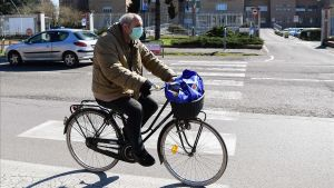Un hombre con mascarilla pasa con su bicicleta.