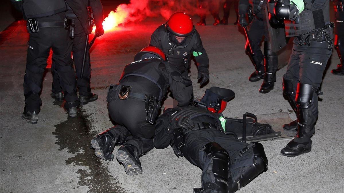 Varios antidisturbios atienden al 'ertzaina' que ha fallecido poco después en el Hospital de Basurto, tras la batalla campal cerca de San Mamés.