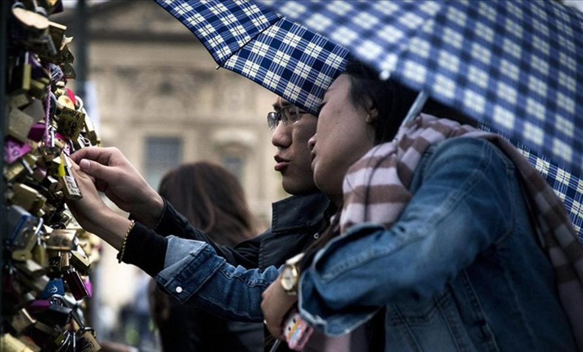 Una pareja de turistas chinos pone un candado en el puente de las Artes, de París, el 31 de mayo del 2015, un día antes de que las autoridades de París retiraran todos los candados de la estructura del puente.