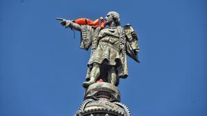 Un activista de Open Arms, encaramado a la estatua de Colón.