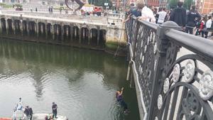 Bomberos izan a una feminista suspendida del puente del ayuntamiento de Bilbao como protesta contra las violaciones.