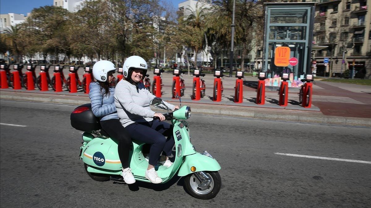 Dos usuarias de moto compartida pasan por delante de una parada del Bicing.