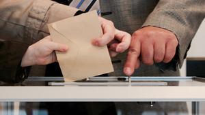 Electores depositan el sobre con el voto en una urna.