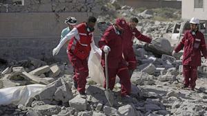 Los servicios de emergencia sacan un cadáver de los escombros del centro de detención bombardeado por Arabia Saudí en Yemen.