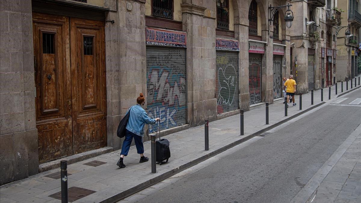 Varios establecimientos del barrio Gòtic de Barcelona, con la persiana bajada, un día laborable al mediodía de julio del 2020.
