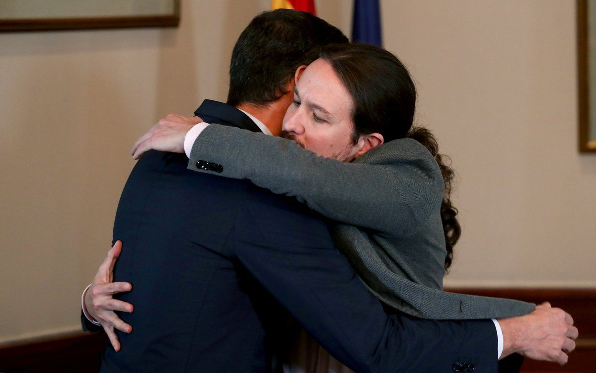 Spanish acting Prime Minister Pedro Sanchez and Unidas Podemos (Together We Can) leader Pablo Iglesias hug during a news conference at Spain's Parliament in Madrid, Spain, November 12, 2019. REUTERS/Sergio Perez