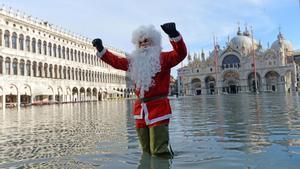 La 'aqua alta'vuelve a inundar Venecia, un hombre vestido de Santa Claus en la Pza. San Marcos.