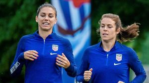 La delantera Alex Morgan y la defensa Kelley O'Hara calientan
