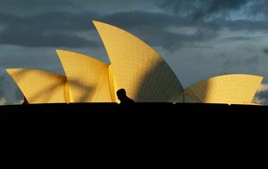 A tourist walks past the Sydney Opera House as a storm approaches overhead at sunset May 30, 2002. Australia's top tourism attraction will receive a $A69 million (US$31 million) make-over during the next six years which will follow designs by the original Danish architect Joern Utzon. The improvements will include the construction of grand columns on the ground level, the orchestra pit will be extended and the seating refurbished, which will mean it will be closed for a year from late 2004.      REUTERS/David Gray
