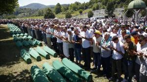 Familiares de víctimas rezan junto a los féretros con restos de las víctimas de Srebrenica identificadas en el 2017.