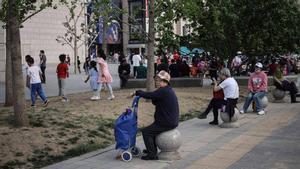 Personas mayores descansan en una calle de Beijing, junto a niños que juegan.