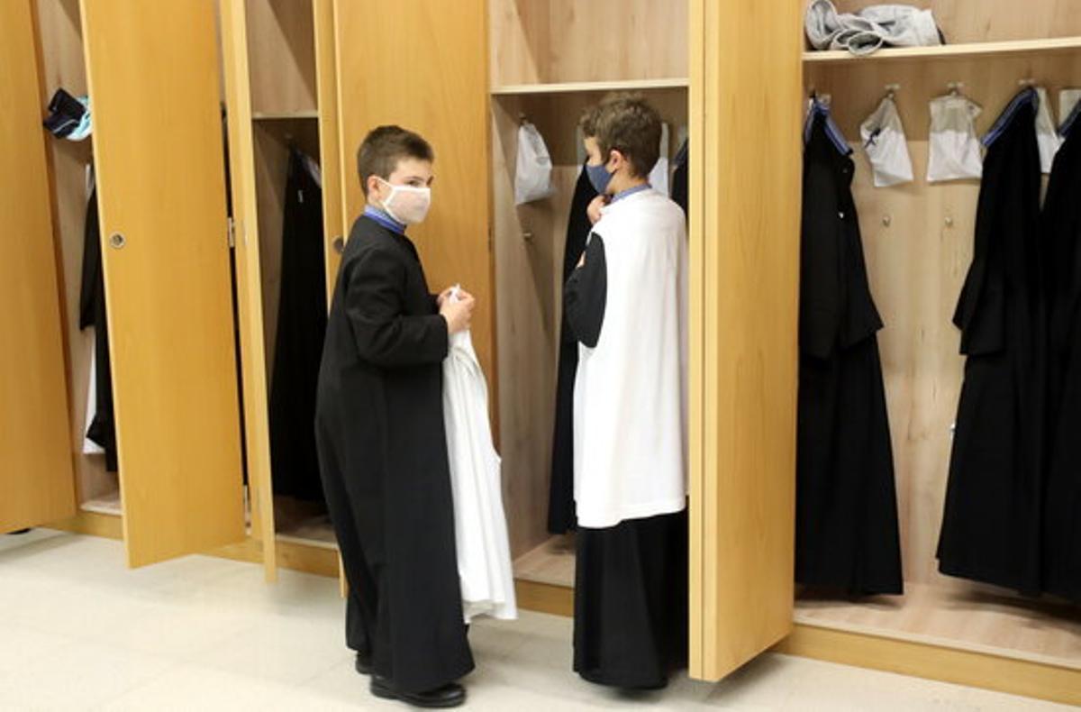 Dos alumnos de la Escolanía de Montserrat se visten para cantar.