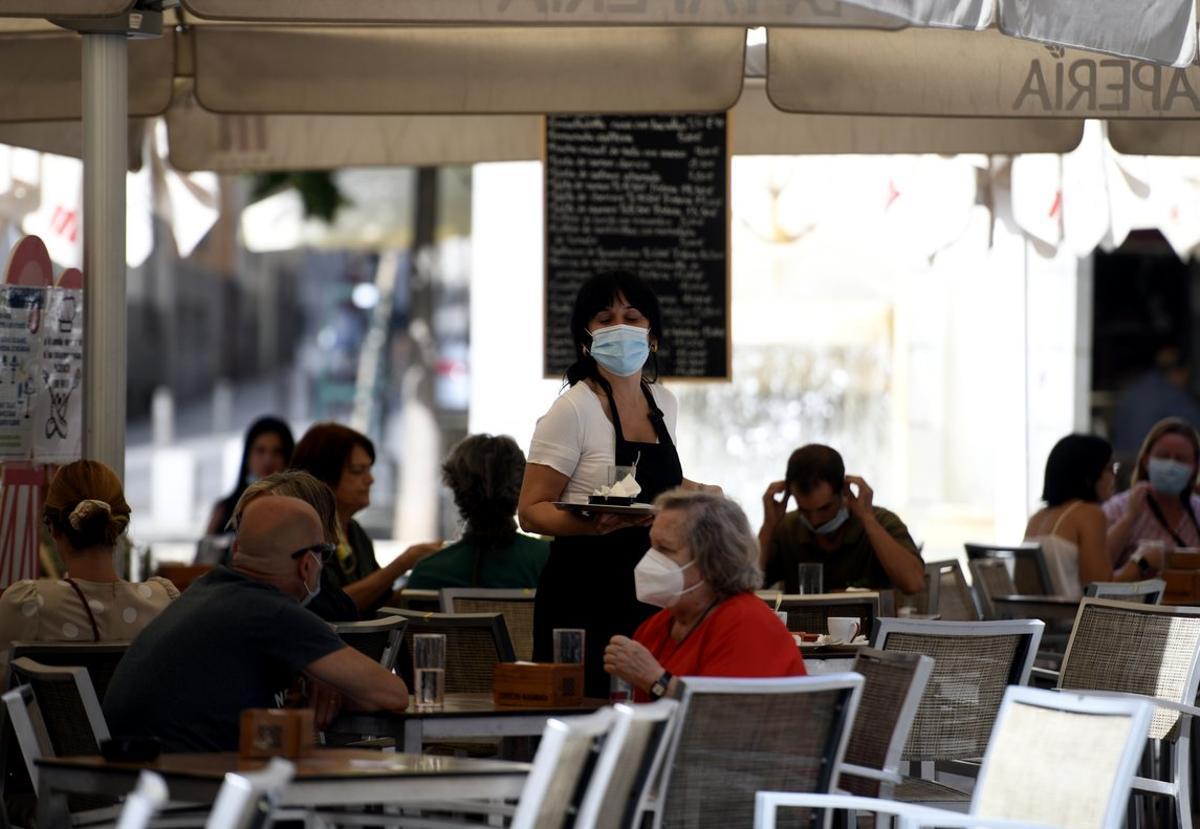 Una camarera atiende a unos clientes en una terraza de Madrid.