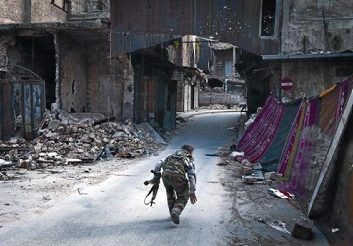 Un rebelde cruza una calle en Alepo intentando eludir a los francotiradores.