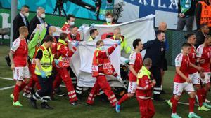 Los jugadores de Dinamarca escoltan la camilla en la que es evacuado Eriksen.