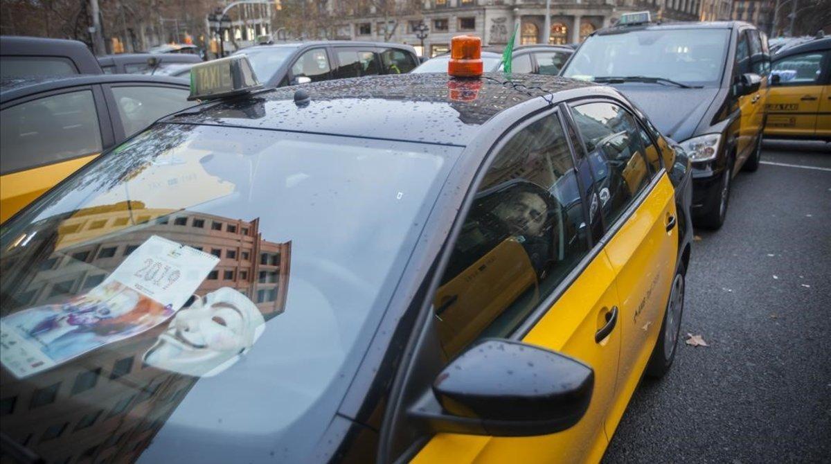 Un taxista descansa en el interior de su vehículo durante la huelga.