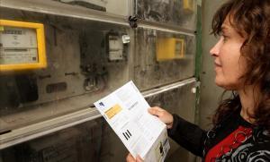 Una mujer consulta una factura de la luz junto a un contador.