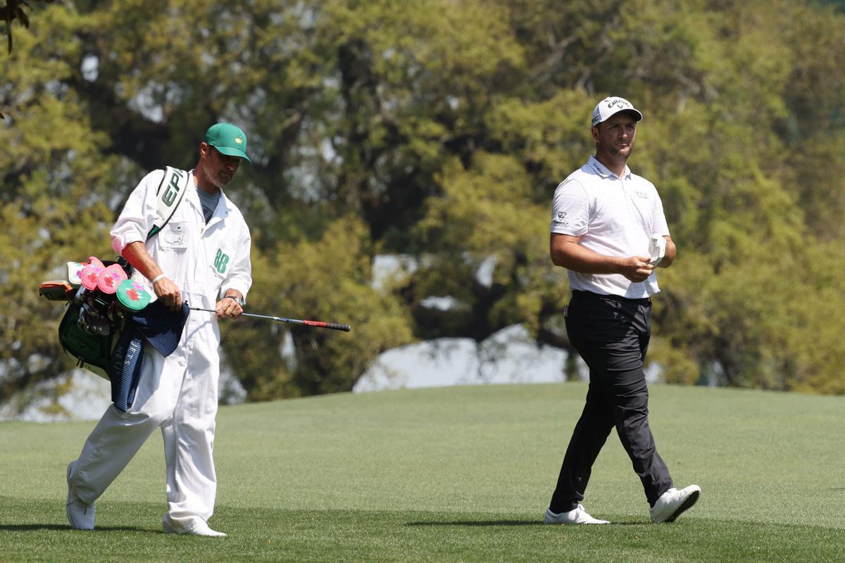 Rahm camina con su caddie, Adam Hayes, en la vuelta de entrenamiento de Augusta