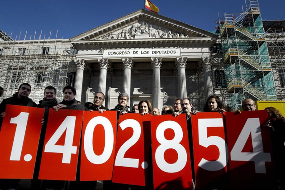 Miembros de la Plataforma de Afectados por la Hipoteca, con una pancarta con la cifra de firmas recogidas en favor de la dación en pago, el pasado 12 de febrero ante el Congreso.