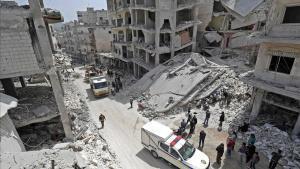 La gente observa a miembros de la Defensa Civil siria buscar entre los escombros de un edificio derrumbado tras una explosión en la ciudad de Jisr al Shughur, en el oeste de la provincia siria de Idleb, bajo control de Hayat Tahrir al Sham.