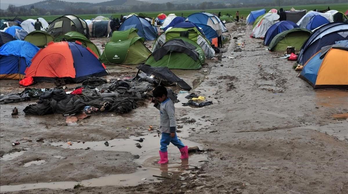 Un niño camina entre el barro en un campo de refugiados próximo a la frontera con Macedonia, cerca de Idomeni (Grecia).