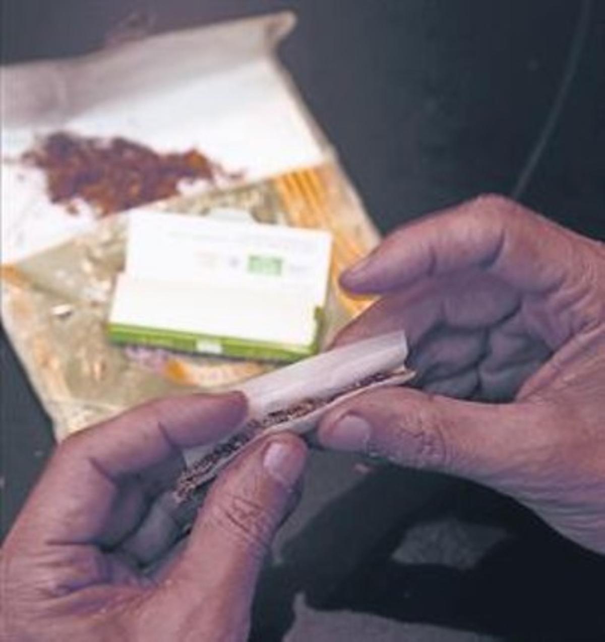 Un hombre lía un cigarrillo, tendencia creciente entre los fumadores.
