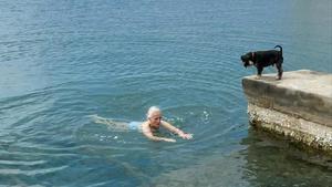 Mercedes Milá, en las aguas de Maó celebrando su cumpleaños, ante la mirada de su perro Scott.
