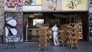 Sillas de una terraza de un bar de Barcelona amontonadas en la puerta, este miércoles.