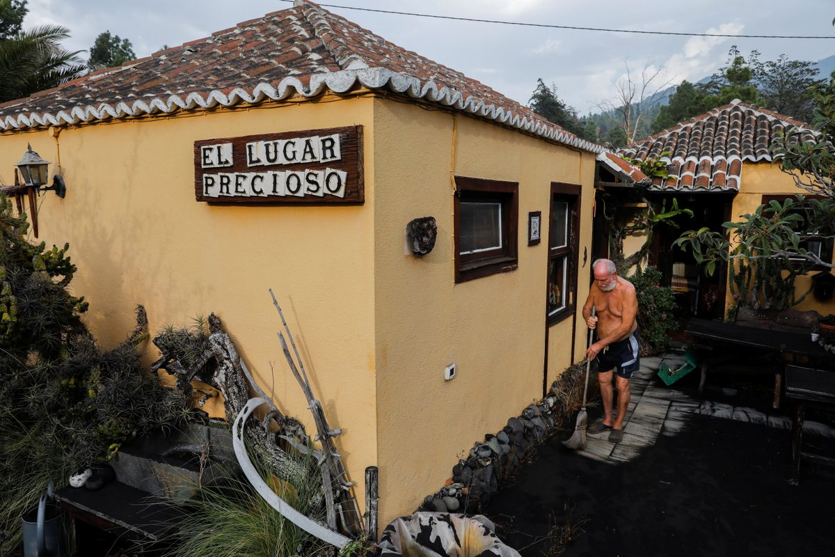 Gert Waegerle limpia la ceniza que cubre la entrada de su casa en Tacande de Arriba. El hombre, de 75 años, fue evacuado de su hogar ante la amenaza del volcán, pero ha podido regresar.