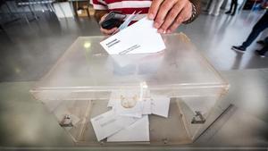 Una persona depositando su voto en la urna.