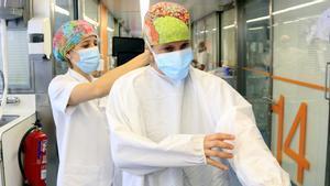 La enfermera de críticos del Hospital Clínic, Raquel González Urria, se viste ayudada por una compañera, para entrar en la UCI.
