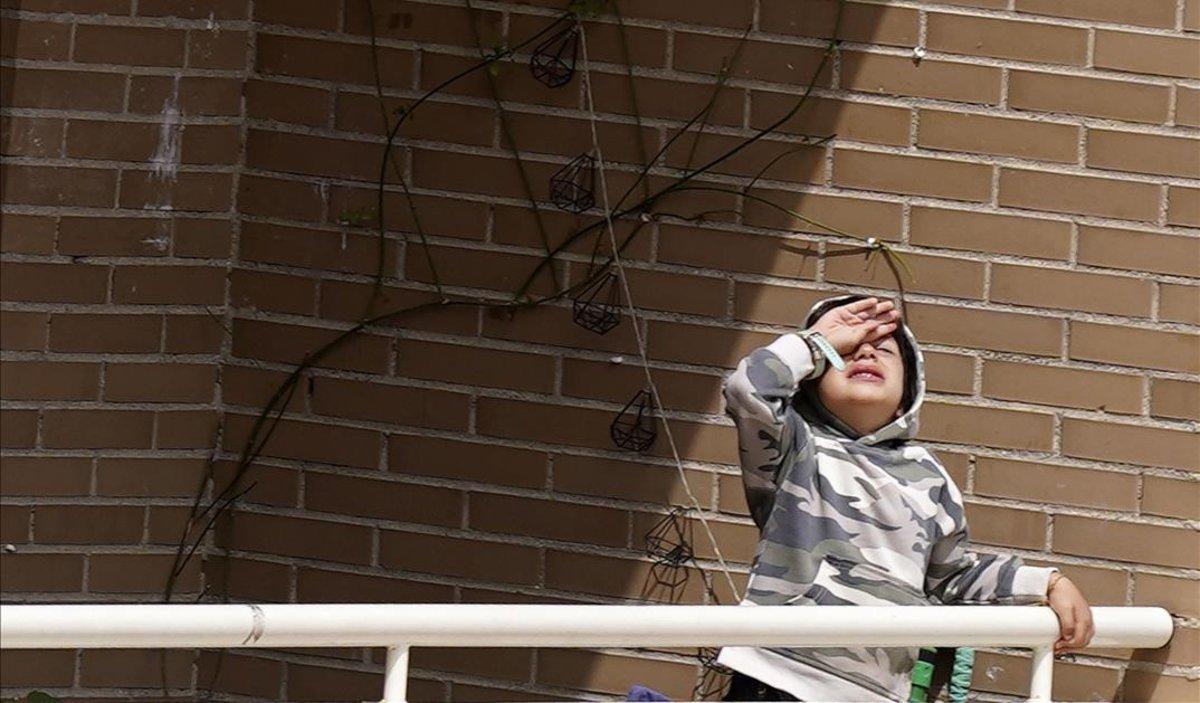 Un niño aburrido en el balcón de su casa, en Madrid.