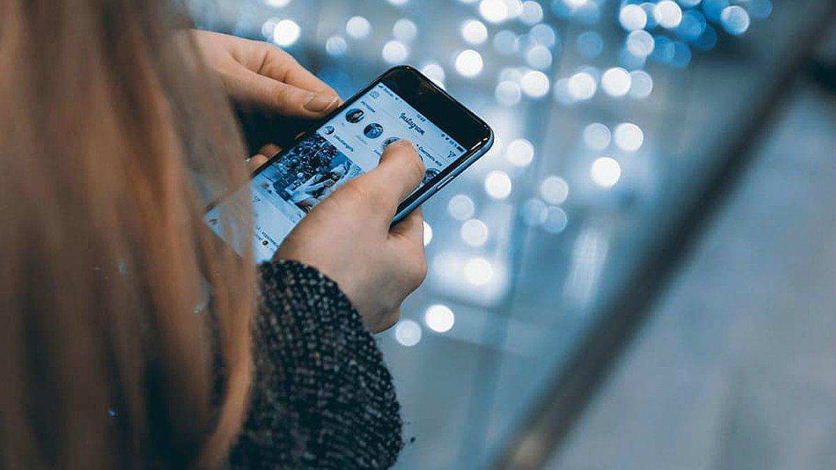Una chica consulta la aplicación en su teléfono móvil de Instagram.